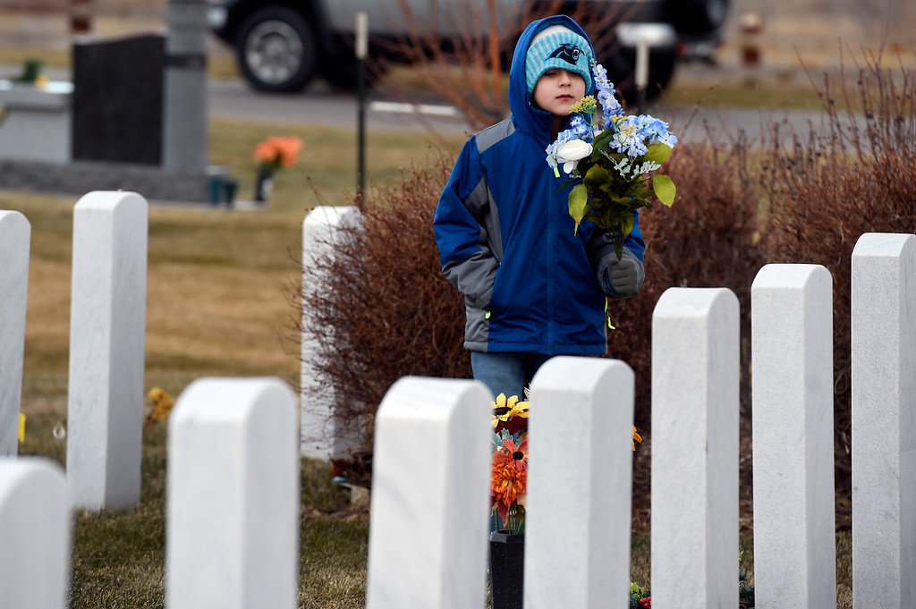 . BROOMFIELD, CO - December 15, 2018: Jackson Head, 9, replaces flowers on a headstone at the Broomfield County Commons Cemetery on December 15, 2018. The Broomfield Rotary Club held a wreath-laying ceremony at Broomfield\'s two cemeteries. Wreaths are meant to honor veterans in all branches throughout the holidays. For more photos, go to dailycamera.com.  (Photo by Cliff Grassmick/Staff Photographer)
