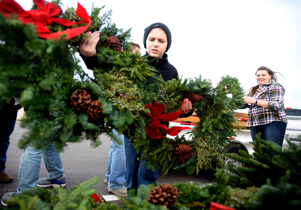 . BROOMFIELD, CO - December 15, 2018: Connor Duggan, 10, and his mother Samantha, prepares the wreaths that will be sit out at the Broomfield County Commons Cemetery on December 15, 2018. The Broomfield Rotary Club held a wreath-laying ceremony at Broomfield\'s two cemeteries. Wreaths are meant to honor veterans in all branches throughout the holidays. For more photos, go to dailycamera.com.  (Photo by Cliff Grassmick/Staff Photographer)