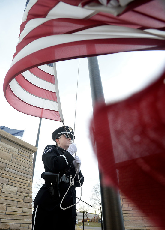 . BROOMFIELD, CO - December 15, 2018: Caitlyn Hollifield, of Broomfield Police, lowers the flag to half mast at the BroomfieldCounty Commons Cemetery on December 15, 2018. The Broomfield Rotary Club held a wreath-laying ceremony at Broomfield\'s two cemeteries. Wreaths are meant to honor veterans in all branches throughout the holidays.  (Photo by Cliff Grassmick/Staff Photographer)