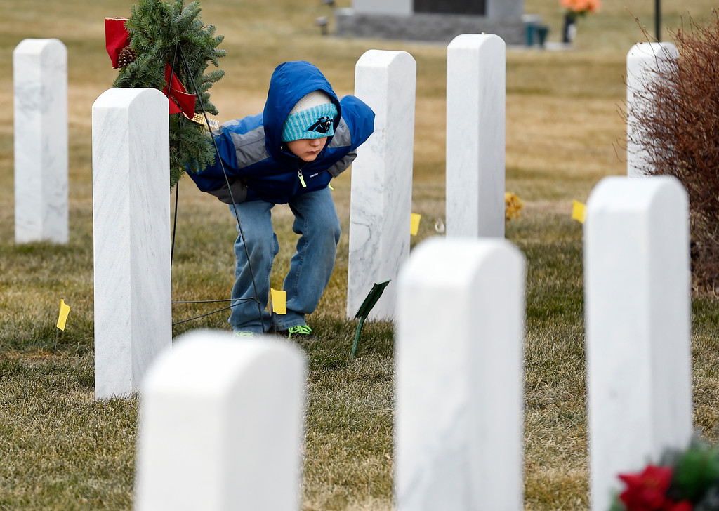 . BROOMFIELD, CO - December 15, 2018: Jackson Head, 9, looks closer at  a headstone at the Broomfield County Commons Cemetery on December 15, 2018. The Broomfield Rotary Club held a wreath-laying ceremony at Broomfield\'s two cemeteries. Wreaths are meant to honor veterans in all branches throughout the holidays. For more photos, go to dailycamera.com.  (Photo by Cliff Grassmick/Staff Photographer)