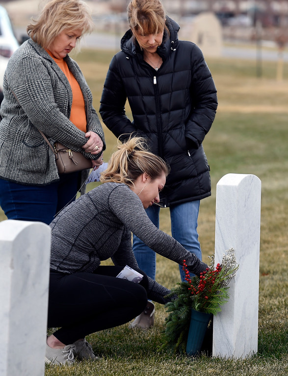 . BROOMFIELD, CO - December 15, 2018: Annie Klauck, bottom, puts a wreath at her father\'s gravesite with her mother, Patty Klauck, left, and her aunt, Marty Paluch, at the Broomfield County Commons Cemetery on December 15, 2018. The Broomfield Rotary Club held a wreath-laying ceremony at Broomfield\'s two cemeteries. Wreaths are meant to honor veterans in all branches throughout the holidays. For more photos, go to dailycamera.com.  (Photo by Cliff Grassmick/Staff Photographer)