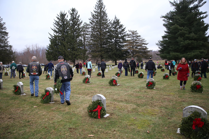 HOLLY PELCZYNSKI - BENNINGTON BANNER Folks walk around the gravesites of fallen soldiers on Saturday morning while at the Vermont Veterans Home during the wreaths across America event in Bennington.