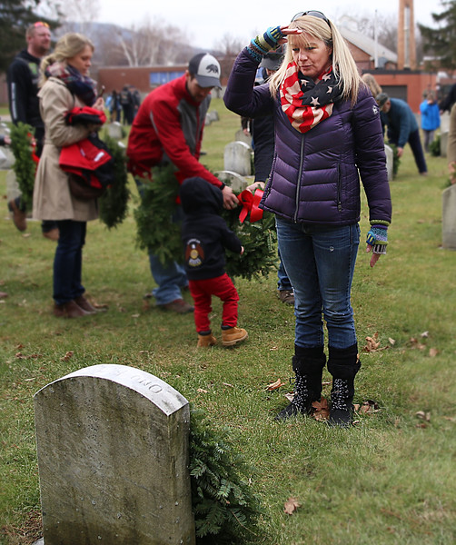 HOLLY PELCZYNSKI - BENNINGTON BANNER Robin Green of Pownal Vermont salutes a grave site after laying a wreath down on Saturday morning at the Vermont Veterans Home during the wreaths across America event.