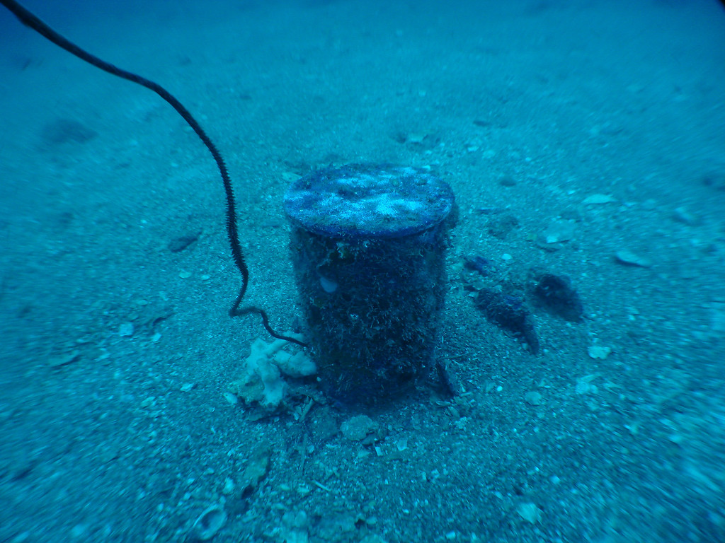 Large shell casing stuck upright in sand
