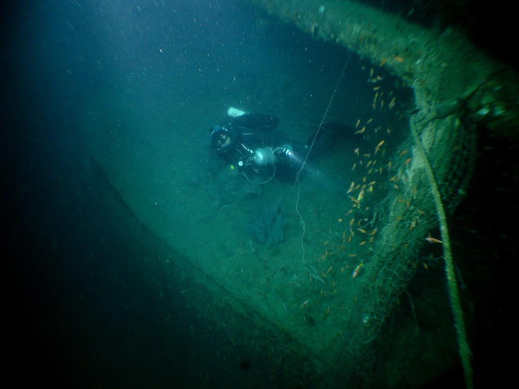 Craig swims under one of the stern guns