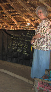Lisa Deeley Smith, one of the directors of Village Help for South Sudan, starts her first teacher-training session for Wunlang schoolteachers. The portable chalkboard is being used in Wunlang's church. We needed to meet there so we could hold the chalkboard in place with bricks at the top of the wall.