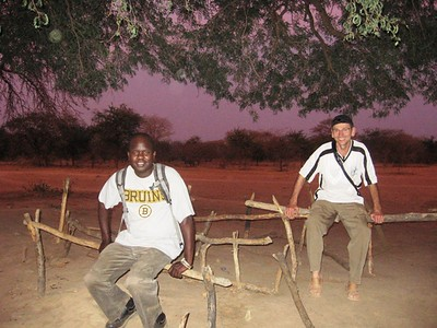 Franco Majok, executive director of Village Help for South Sudan, and Ron Moulton, treasurer, sit on the benches of a classroom of a school under the trees in Wunlang.