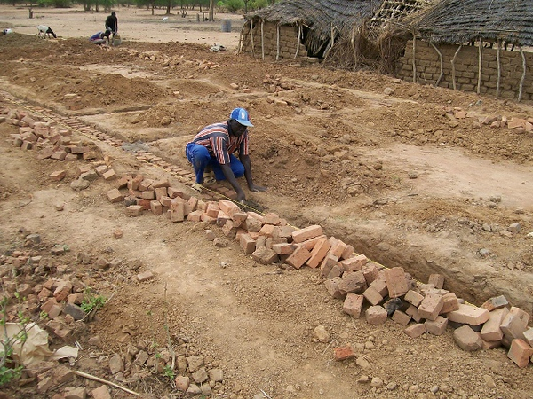 Laying the first bricks atop the foundation. The collapsing Wunlang Church is in the background.