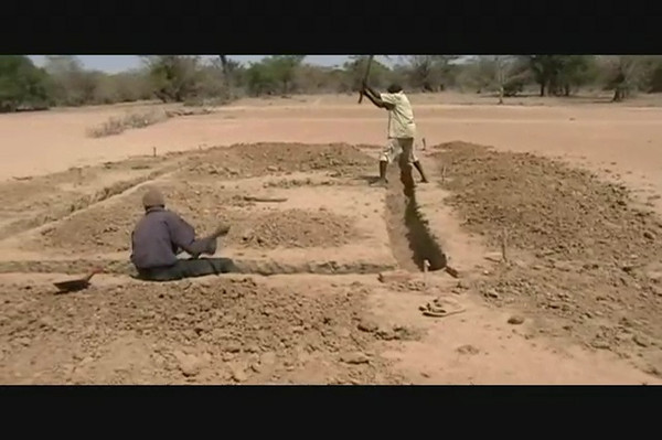Two workers begin the excavation of the foundation of Wunlang School, and then our treasurer Ron Moulton lends a hand.