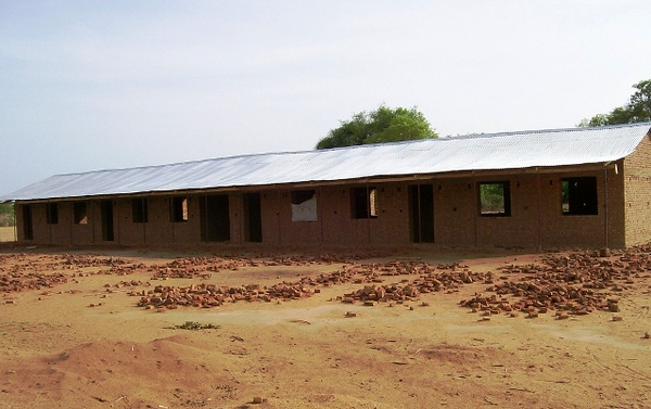 One of two four-classroom blocks, roofed and waiting for its outside coat of cement and paint.