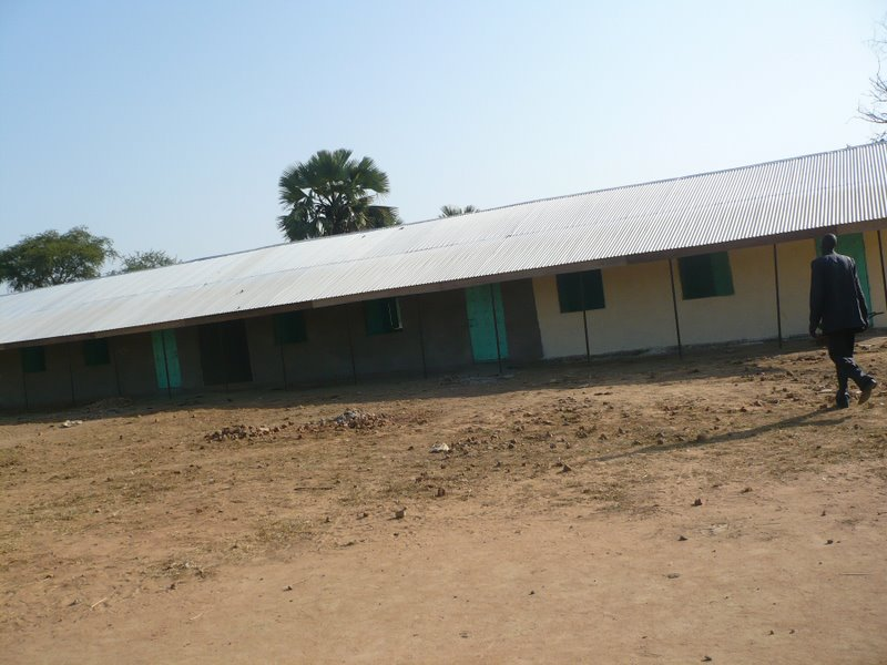 Our field manager Yel approaches one of our two classroom blocks, which is halfway stuccoed.