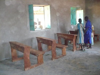 """Students inspect the newly-installed desks in a classroom. Go to our """"School's Open"""" gallery to see the desks in use!"""