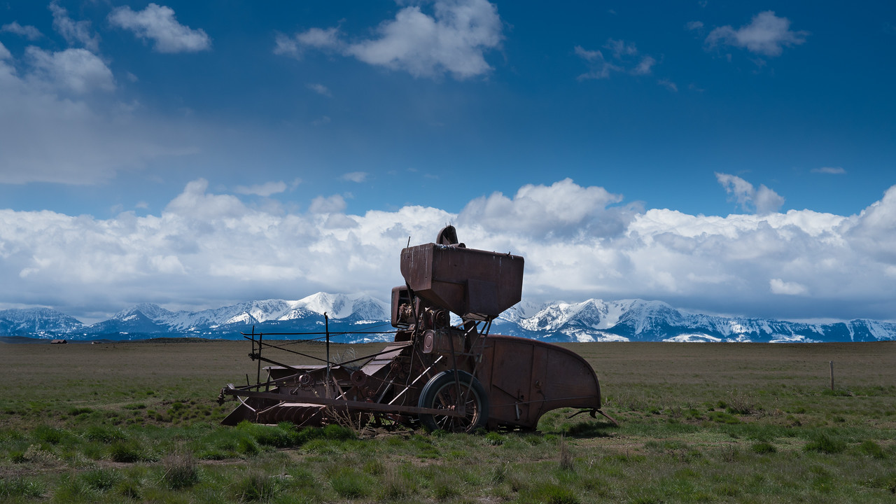 Old combine with the Bridger mountains in the background.