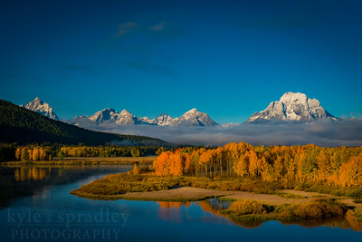 A fall sunrise at the infamous Oxbox Bend in Grand Teton National Park. The peaks of the Teton Range rise above the Snake River that meanders past golden canopies of cottonwoods and aspens just below Jackson Lake.    © Kyle Spradley Photography | www.kspradleyphoto.com