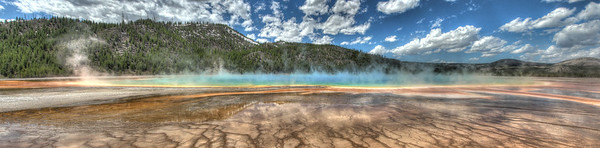The Grand Prismatic Spring in Yellowstone National Park.   It's amazing how clear and blue the spring waters are, which lends to its name.  Its liquid colors are only matched by the rainbow dispersion of sunlight into a prism of reds, oranges, yellows, greens, and blues.  The edges are also tainted with red to green colored bacteria that grow around the mineral rich waters.