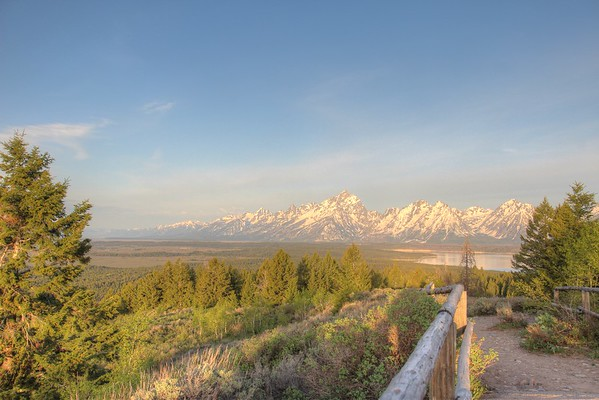 As the sun rises it baths the Teton Range and valley in a swath of golden hues.