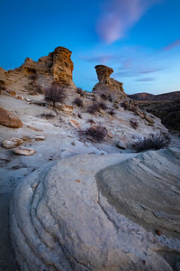 Rock formations near the Lost Creek Draw area of Sinclair, Wyoming. Located in Carbon County, the sculpted land is a rugged, moonlike ecosystem scattered with sagebrush and sparse plant life. Looking to the south, Cedar Ridge rises above the formations.   Photo by Kyle Spradley | © Kyle Spradley Photography | www.kspradleyphoto.com