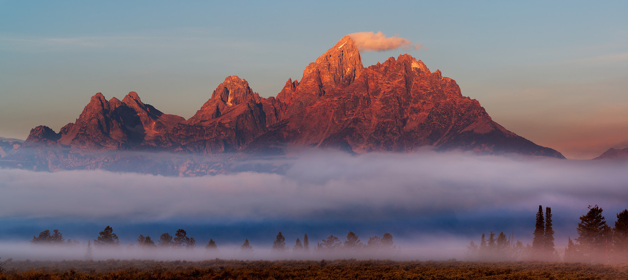 Dawn light on the Teton Mountain range, with fog shrouded conifers beneath the crimson lit Grand Teton.  Grand Teton National Park, Wyoming.