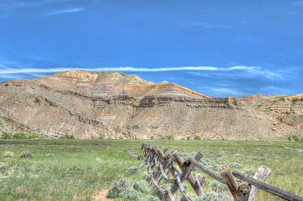 A split rail fence crisscrosses the sage brush covered ground and rainbow hued hills climb skyward in the background.
