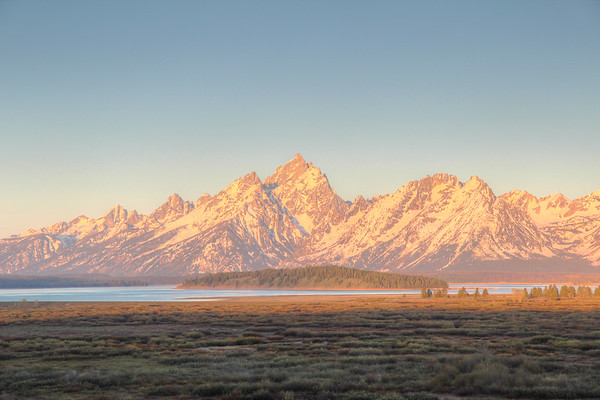 The rising sun paints the Teton range and valley a brilliant golden color.