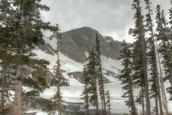 The Snowy Range stands tall behind a frozen Lake Marie in the Medicine Bow National Forest.
