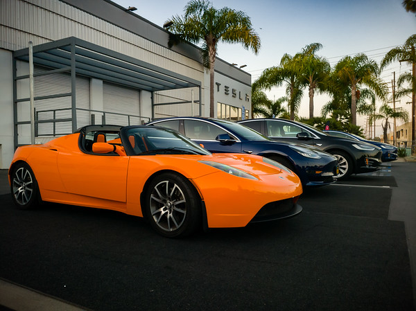 The full range of Tesla vehicles are in attendance, including this bright orange roadster
