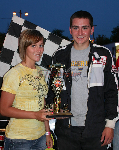 California's Brant Koetting claims his first 2009 street stock feature trophy. Missy Gerhart of Mr. G's Packaged Liquor, California MO, serves as Double-X Speedway trophy girl. Photo by Carol Wirts of Double-X Speedway - California MO
