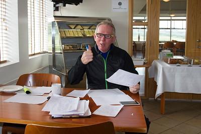 David Barnwell, golfkennari GR sinnir pappírsvinnu. Á blöðunum eru upplýsingar um æfingahópa unglinga í klúbbnum.