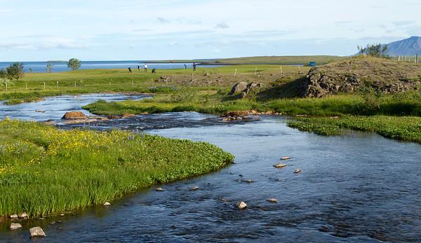 Kylfingar við leik á þriðju flöt. Áin í forgrunni en hún rennur til sjávar, skammt norðan við flötina.