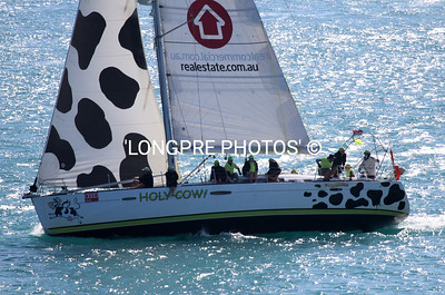 HOLLY COW finishing in front of HAMILTON ISLAND YACHT CLUB.