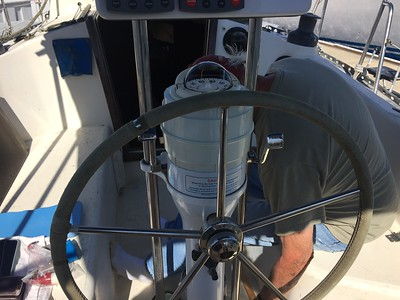 Wheel steering, center is tightening knob, showing engine controls on each side of the binnacle.