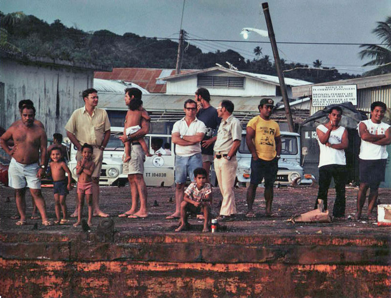 """On the dock in Colonia (left to right):  John Mangefel (Senator), Mike Allen (Land Manager), Mike McCoy (Marine Resources) and daughter Cindy, Wally Kluver (Bank Manager), Herald Timme (Weather Station Manager), Sonny Honeycutt (PCV), Sam Falenruw (Peace Corps Director), Francis """"The Wolfman"""" (Yap Radio DJ), John Hagelalegam (later President of the FSM). Sign on the right notifies incoming passengers that Drinking Permits are required in Yap District."""