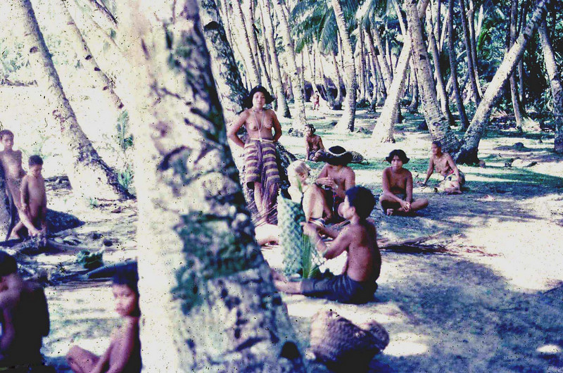 """Susan:  """"Day of the big fish catch on Ifalik:  Mary Jane Mortimer (Micro 7) seated among women and children, to the right of the tree in the foreground"""""""