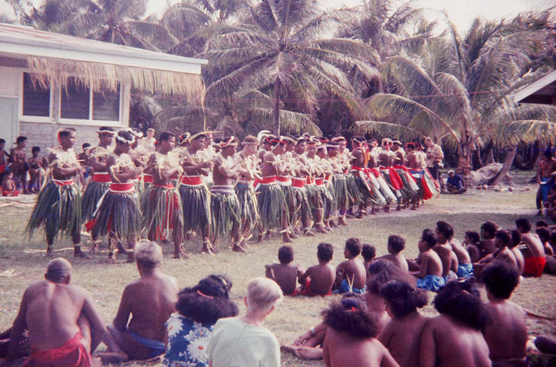 Men's dance, with Len Menzie, Micro 7 PCV, in the front row, fifth from the left.  In the foreground, seated in the center among the spectators, back to camera, Ulithi teacher, Mrs. Stahl