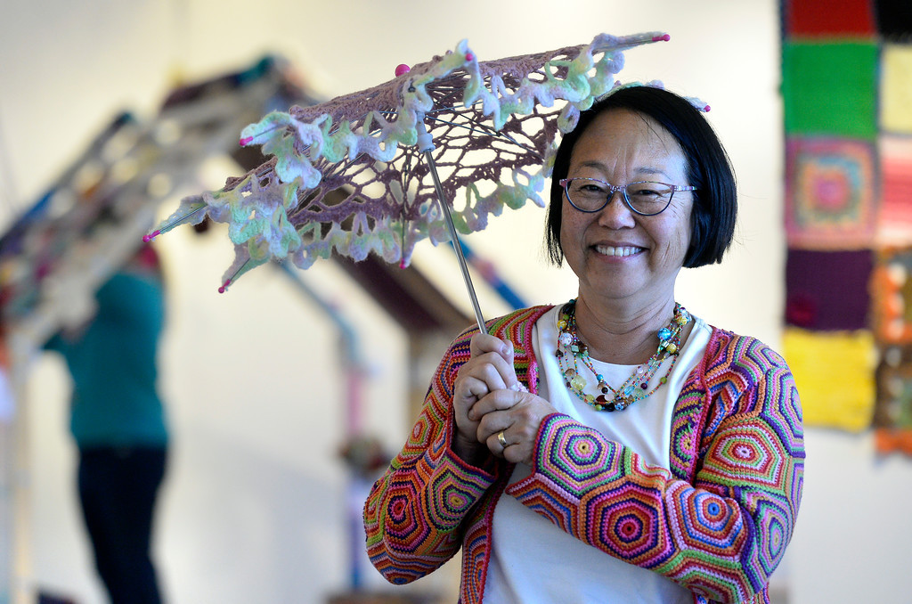 . BOULDER, CO - NOVEMBER 8, 2018: Louise Garrels holds a crocheted umbrella she created while setting up the Yarn-Fiti exhibit on Thursday inside the Boulder Public Library in Boulder. For more photos of the Yarn-Fiti exhibit and volunteers go to dailycamera.com (Photo by Jeremy Papasso/Staff Photographer)