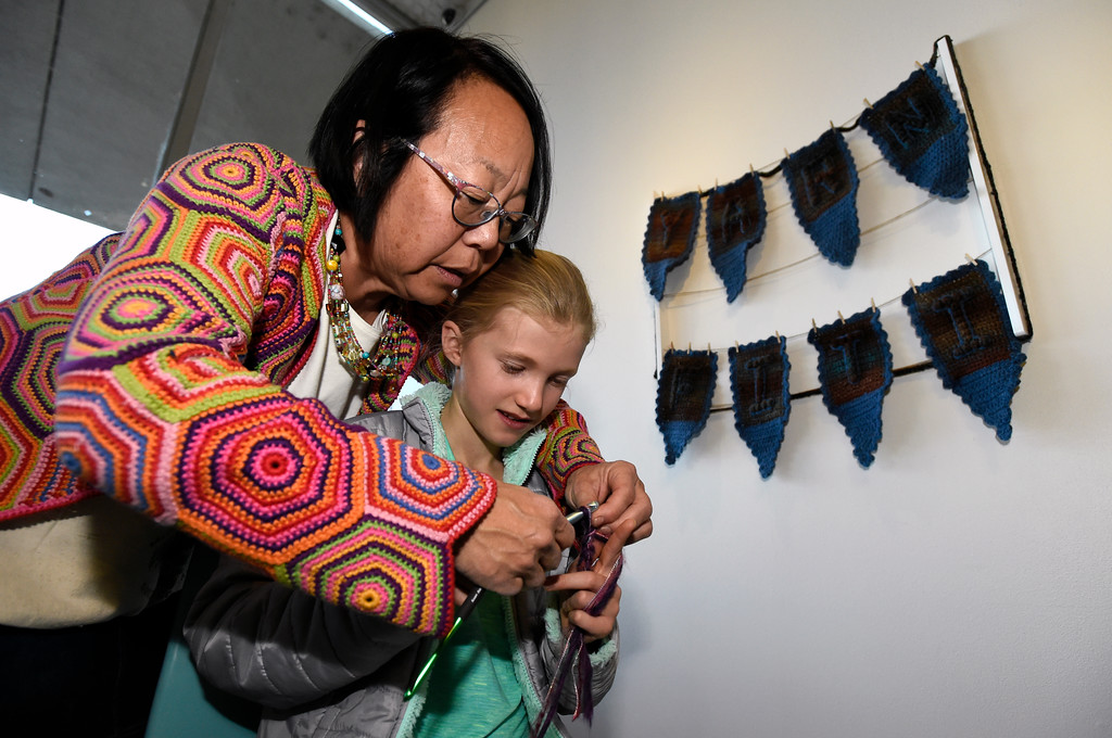 . BOULDER, CO - NOVEMBER 8, 2018: Louise Garrels teaches Willow Gilmartin, 9, how to crochet while setting up the Yarn-Fiti exhibit on Thursday inside the Boulder Public Library in Boulder. For more photos of the Yarn-Fiti exhibit and volunteers go to dailycamera.com (Photo by Jeremy Papasso/Staff Photographer)