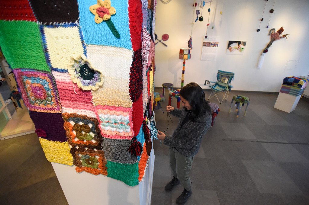 . BOULDER, CO - NOVEMBER 8, 2018: Allison Hybertson attaches crocheted and knitted squares to a piece of art while setting up the Yarn-Fiti exhibit on Thursday inside the Boulder Public Library in Boulder. For more photos of the Yarn-Fiti exhibit and volunteers go to dailycamera.com (Photo by Jeremy Papasso/Staff Photographer)