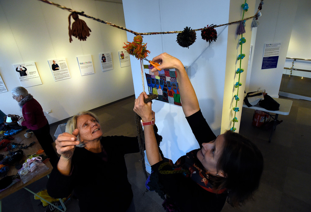 . BOULDER, CO - NOVEMBER 8, 2018: Lynda McGinley, left, and Louise Fordyce work to set up the Yarn-Fiti exhibit on Thursday inside the Boulder Public Library in Boulder. For more photos of the Yarn-Fiti exhibit and volunteers go to dailycamera.com (Photo by Jeremy Papasso/Staff Photographer)