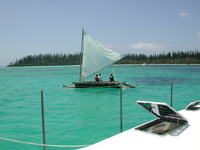Nov, 2000: Oro Bay, Isle des Pines, New Caledonia: a Piroque sails past Adagio, with guests from the 5* Merdien resort.
