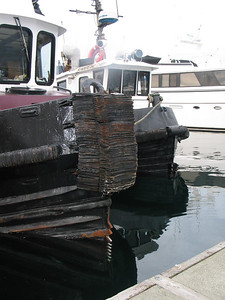 """Log dozers"" are tugs for pushing around logs in log booms. Notice the metal ""teeth"" near the waterline."