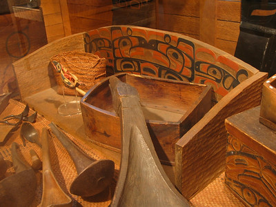 Clockwise from upper left corner: carved wooden rattle, woven bag for gathering shellfish, chief's seat, bentwood box  and carved spoons at the Museum of Northern British Columbia, Prince Rupert