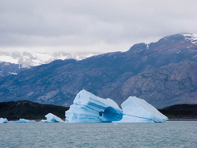 Snowfields of the Andes in the distance,  and local fjord mountains in the mid zone, frame this large ice berg.