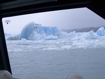This is a view of a berg through a window in the passenger space of the boat.