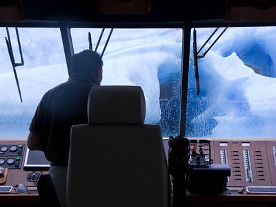 I snapped a shot of the captain as he was maneuvering the boat up to this berg.