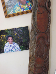 Wood carving beside the photo of a village elser in the visitor center in the village of Vao in the Isle of Pines