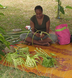 A Kunie woman was weaving baskets, hats and flags from pandanus tree leaves.