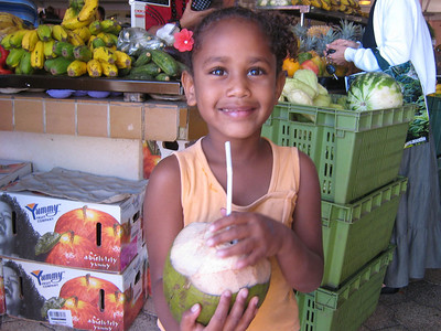 Beautiful little girl drinking from a fresh coconut at the Farmers' Market