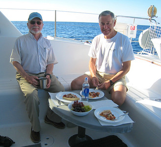Steve and Shaun Peck dining in the cockpit at sea.