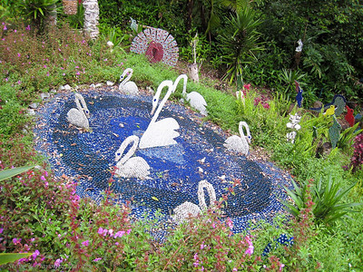 Swans swimming a pond, all made from jewels.