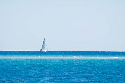 Another boat was sailing on the other side of the sandbar